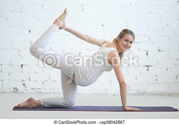 pregnant young woman doing prenatal sunbird yoga pose