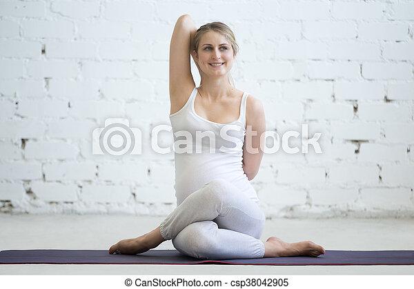 pregnant young woman doing prenatal yoga gomukhasana pose