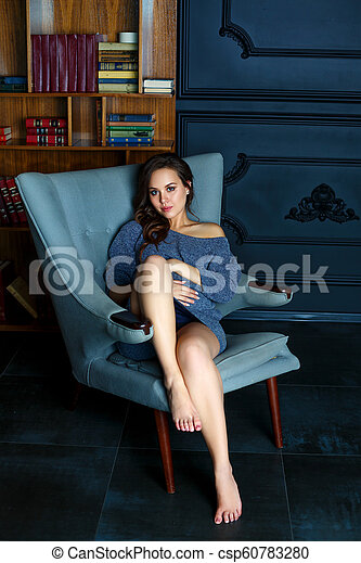 pregnant young woman sitting in a chair - csp60783280
