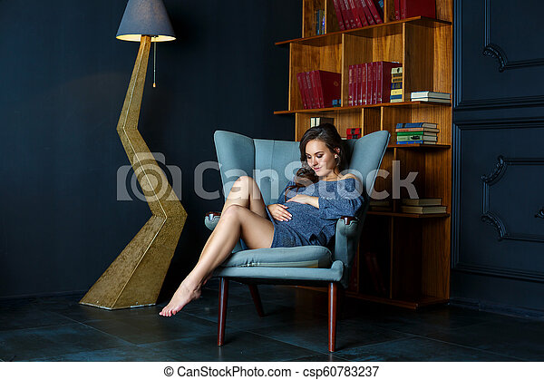 pregnant young woman sitting in a chair - csp60783237