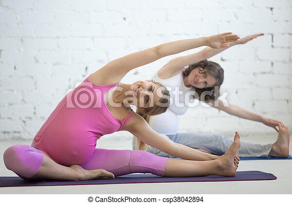 pregnant young women doing prenatal yoga headtoknee