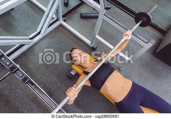 Una mujer con pesas en un entrenamiento de prensa - csp28800591