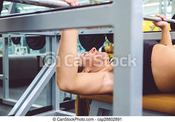 Una mujer con pesas en un entrenamiento de prensa - csp28802891
