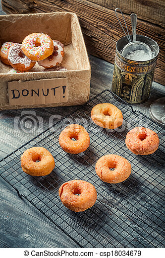 Preparing to decorate donuts with icing sugar - csp18034679