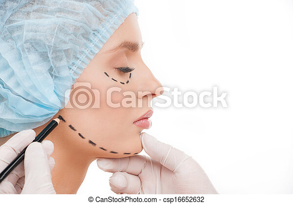 Preparing to plastic surgery. Side view of beautiful young woman in medical headwear and doctors hands marking her face with felt tip pen - csp16652632