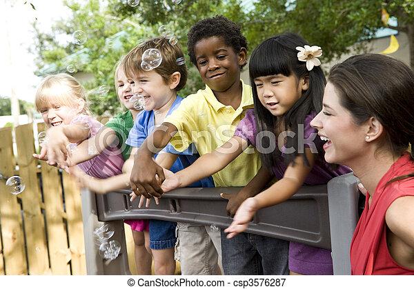 Preschool children playing on playground with teacher - csp3576287