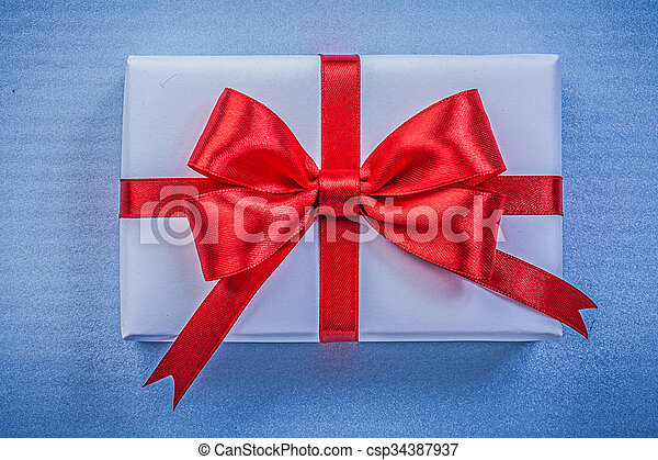 Present on blue background close up view holidays concept - csp34387937