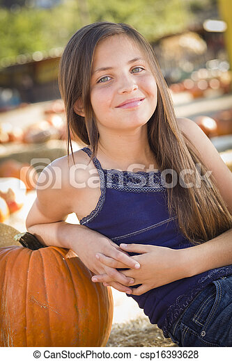 1ede94ab62b Preteen girl portrait at the pumpkin patch in a rustic setting.
