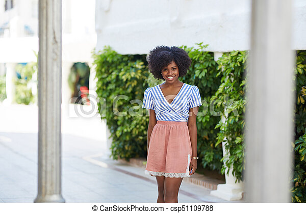 Pretty afro american woman in dress standing outside smiling - csp51109788