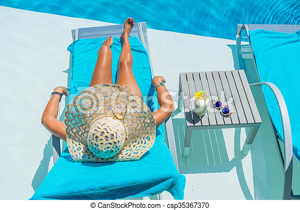 Pretty blond woman a cocktail in a swimming pool - csp35367370
