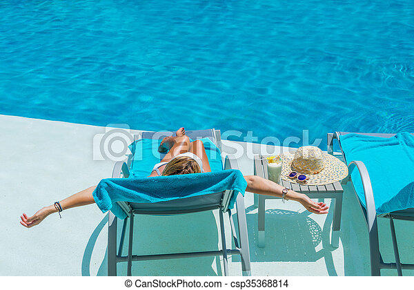 Pretty blond woman a cocktail in a swimming pool - csp35368814