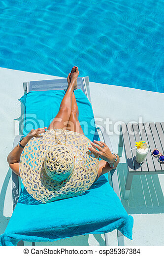 Pretty blond woman a cocktail in a swimming pool - csp35367384