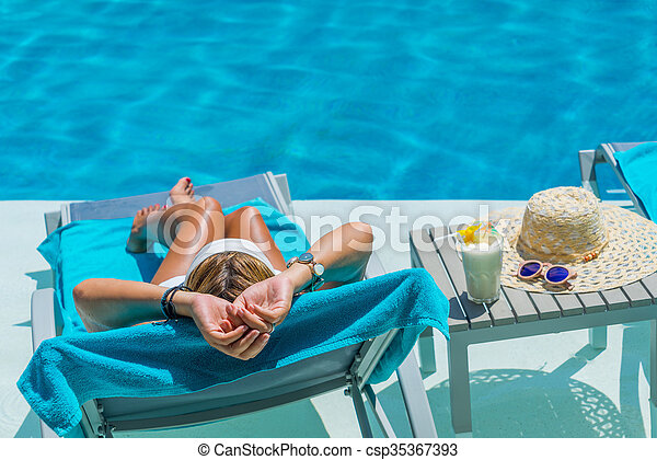 Pretty blond woman a cocktail in a swimming pool - csp35367393