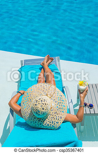 Pretty blond woman a cocktail in a swimming pool - csp35367401