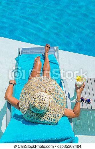 Pretty blond woman a cocktail in a swimming pool - csp35367404