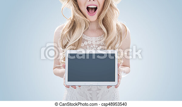 Pretty blond woman holding a tablet - csp48953540
