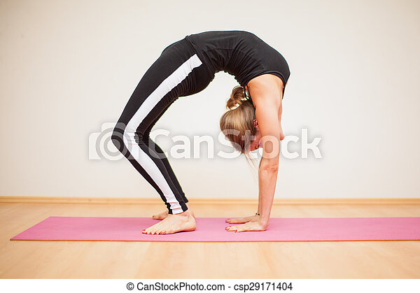 Pretty Blonde Doing Some Yoga Profile View Of A Blond Young Flexible Woman Doing A Difficult Backbend Pose In A Yoga Studio