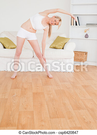Pretty blonde female stretching in the living room - csp6420847