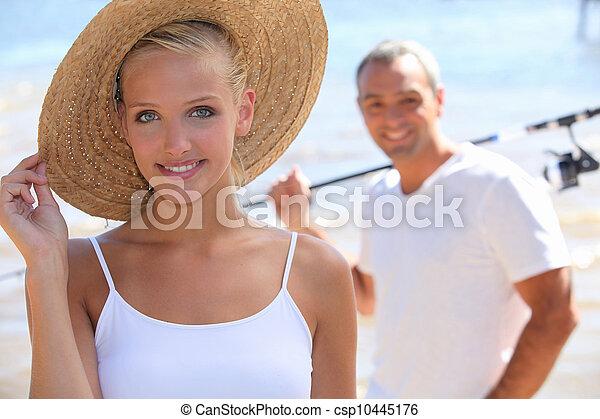 pretty blonde with sun hat and boyfriend in background - csp10445176