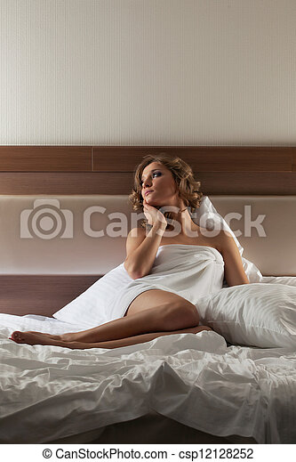 Pretty blonde woman sitting on bed - csp12128252