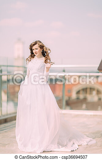 Pretty bride with long curly hair in wedding dress posing on the terrace - csp36694507
