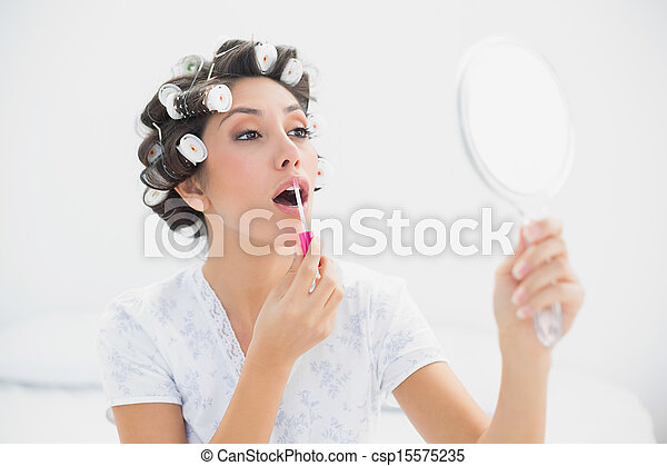 pretty brunette in hair rollers holding hand mirror and applying lip gloss at home bedroom e59 hand