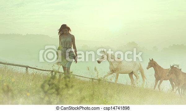 Pretty brunette lady resting among horses - csp14741898