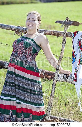 Pretty brunette posing in sundress in a field - csp15203073