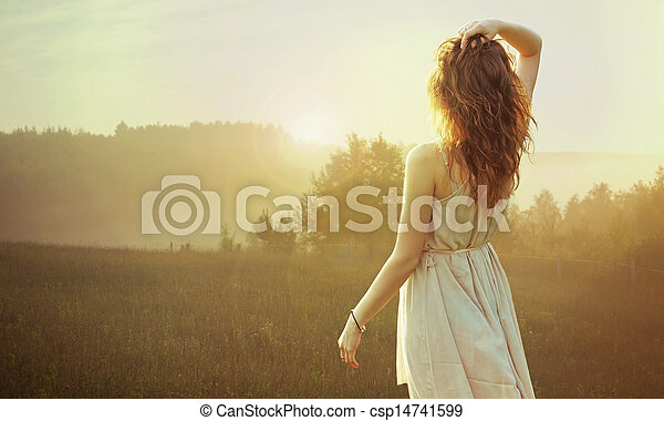 Pretty brunette woman watching the sunset - csp14741599
