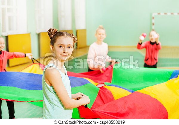 Pretty girl playing parachute games in sports hall - csp48553219