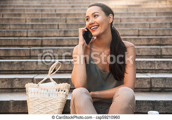 Pretty happy asian woman sitting on steps - csp59210960
