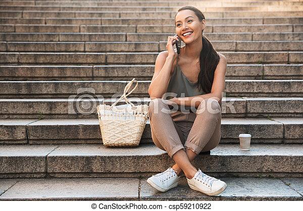 Pretty happy asian woman sitting on steps - csp59210922