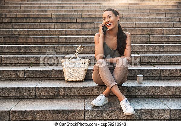 Pretty happy asian woman sitting on steps - csp59210943