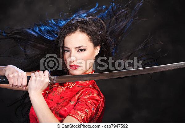 Pretty kimono woman in action with katana/sword - csp7947592