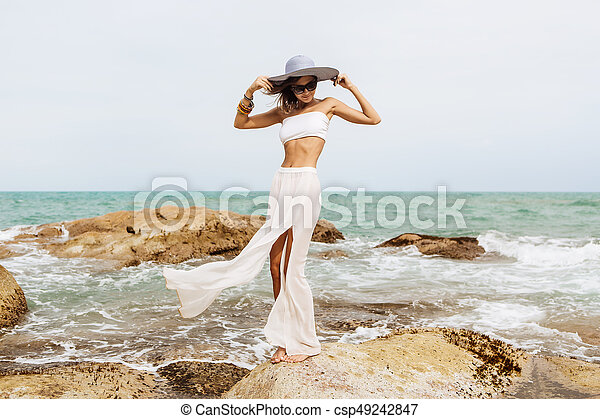 Pretty lady in summer outfit on the beach. Sexy lady stand on rock ... 33d57a4793dc