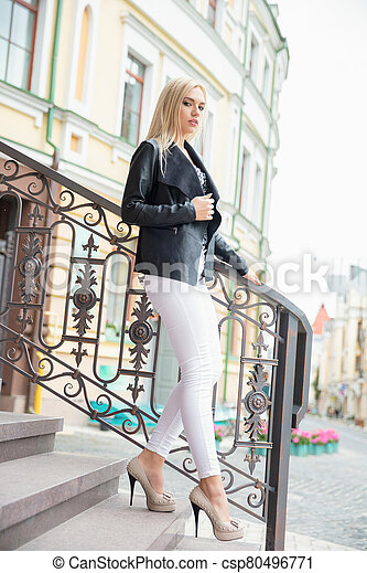 Pretty lady posing while standing on stairs - csp80496771