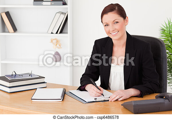 Pretty red-haired woman in suit writing on a notepad - csp6486578