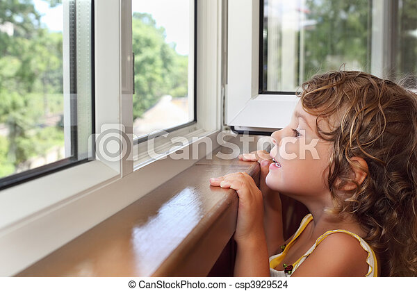 pretty smiling little girl on balcony, look from window - csp3929524