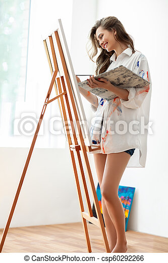 Pretty Woman Artist Painting On Canvas In Art Studio