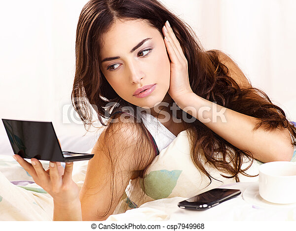 Pretty woman checking face skin in bed, looking at mirror - csp7949968