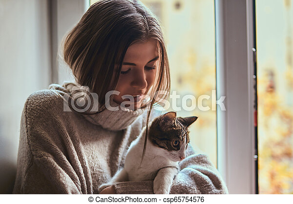 Pretty woman in a warm sweater hugs her favorite cat sitting on the window sill next to the open window - csp65754576