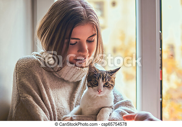 Pretty woman in a warm sweater hugs her favorite cat sitting on the window sill next to the open window - csp65754578