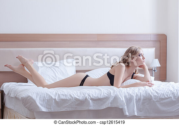 Pretty woman in black lingerie posing on bed - csp12615419