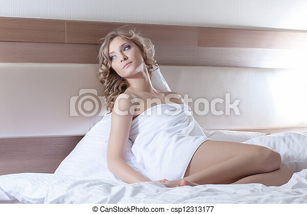 Pretty woman in towel sitting on bed - csp12313177