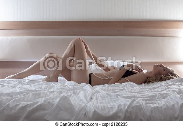 Pretty woman posing in black lingerie on huge bed - csp12128235
