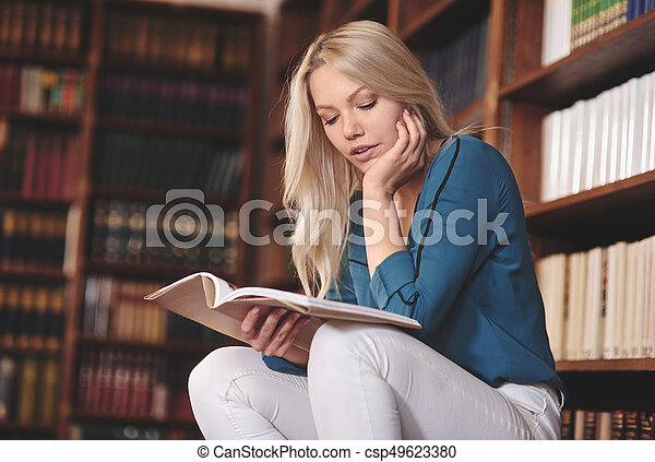 pretty woman reading book in library