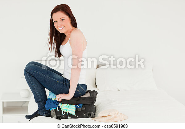 Pretty woman sitting on her suitcase - csp6591963