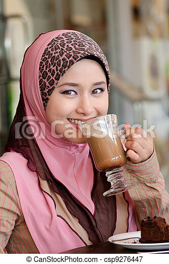 Pretty young Asian Muslim woman with lovely smiles having lunch at coffee shop - csp9276447