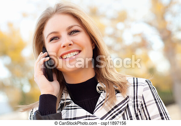 Pretty Young Blond Woman on Phone Outside - csp11897156
