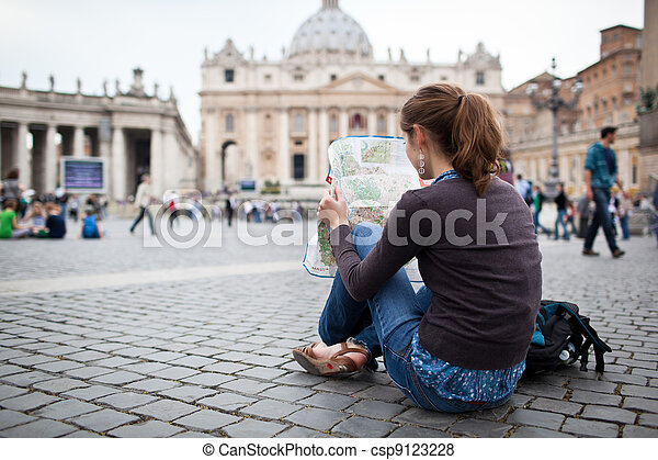 Pretty young female tourist studying a map at St. Peter's square in the Vatican City in Rome - csp9123228